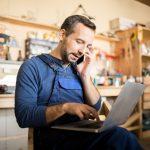 Dueño de pequeño negocio en taller usando laptop y hablando por teléfono. Concepto: cuenta de ahorro comercial