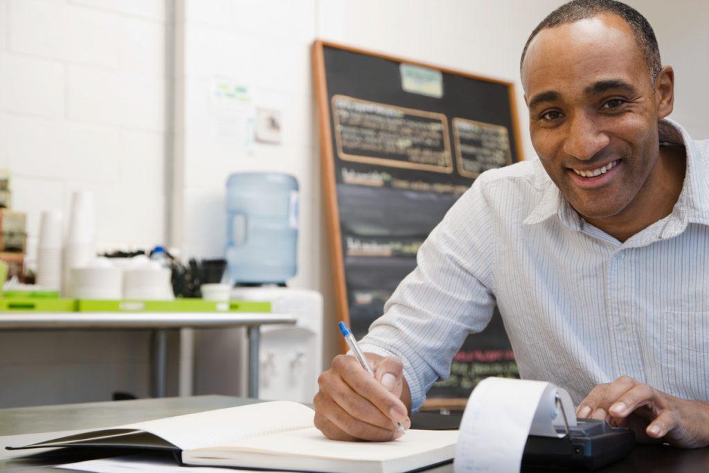 Hombre haciendo la contaduría en una cafetería. Concept: ingresos y ganancias