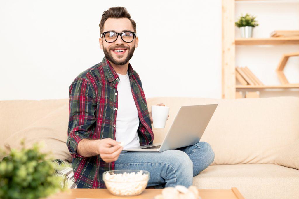 Joven solopreneur trabajando en laptop desde el sofá de su casa. Concepto: Consejos para solopreneurs