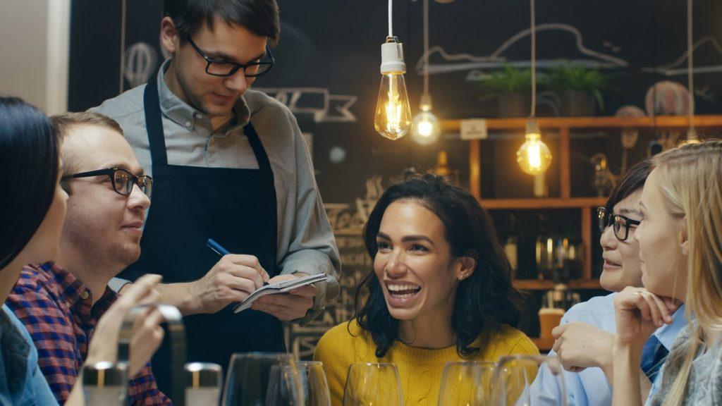 En un restaurante, mesero tomando orden, grupo diverso de amigos tomando vino y divirtiéndose. Concept: ingresos, restaurante