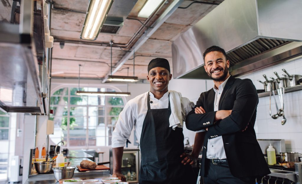 Portrait of restaurant owner with chef in kitchen. Businessman with professional cook standing together and looking at camera. Concept: restaurant revenue