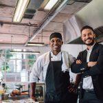 Dueño de negocio sonriente junto con el chef, restaurante, negocio, pequeño negocio. Concept: restaurante, ingresos