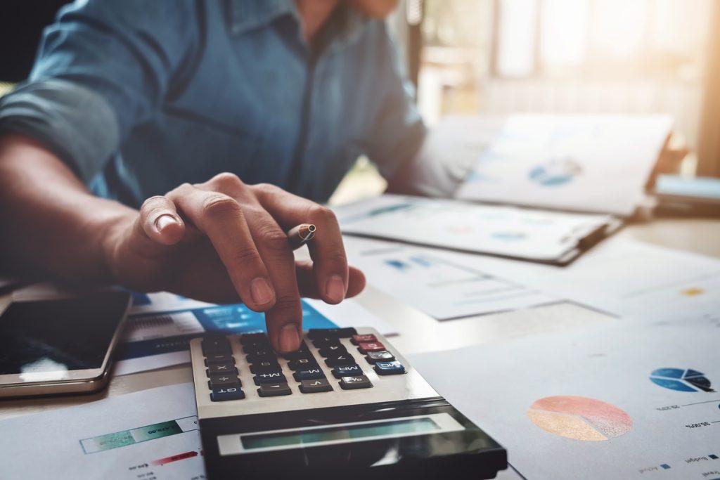 Concepto de contaduría, contador usando calculadora con laptop, dinero, préstamos. Concept: teneduría de libros vs contabilidad