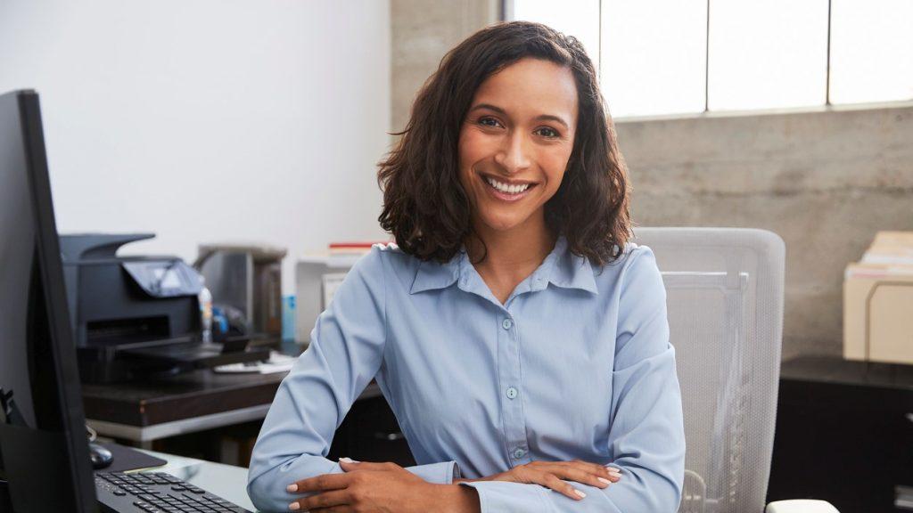 Mujer profesional joven en un escritorio sonriendo. Concept: teneduría de libros y contabilidad