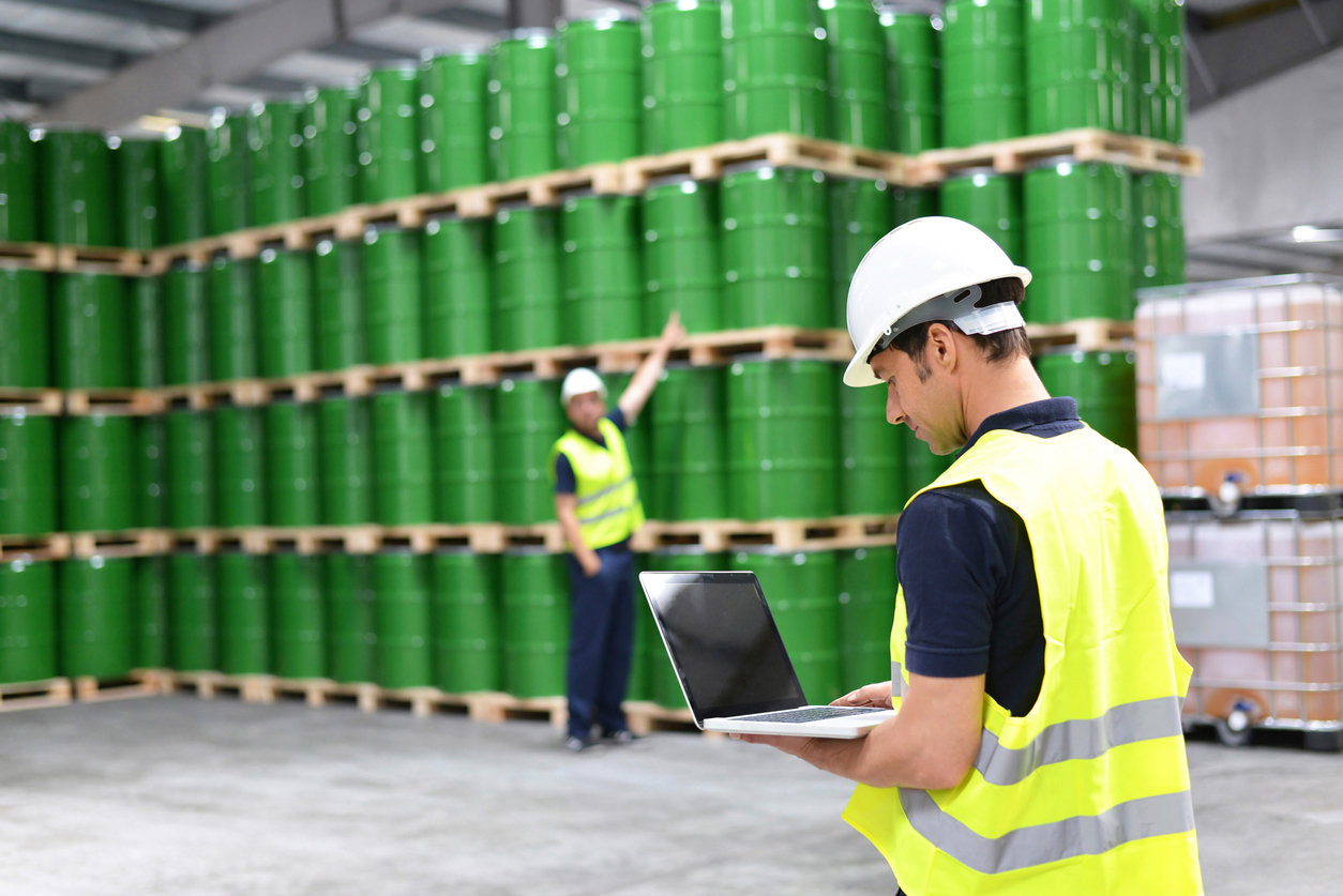 Worker in a warehouse with oil barrels checks the stock. Concept: Inventory Management Software