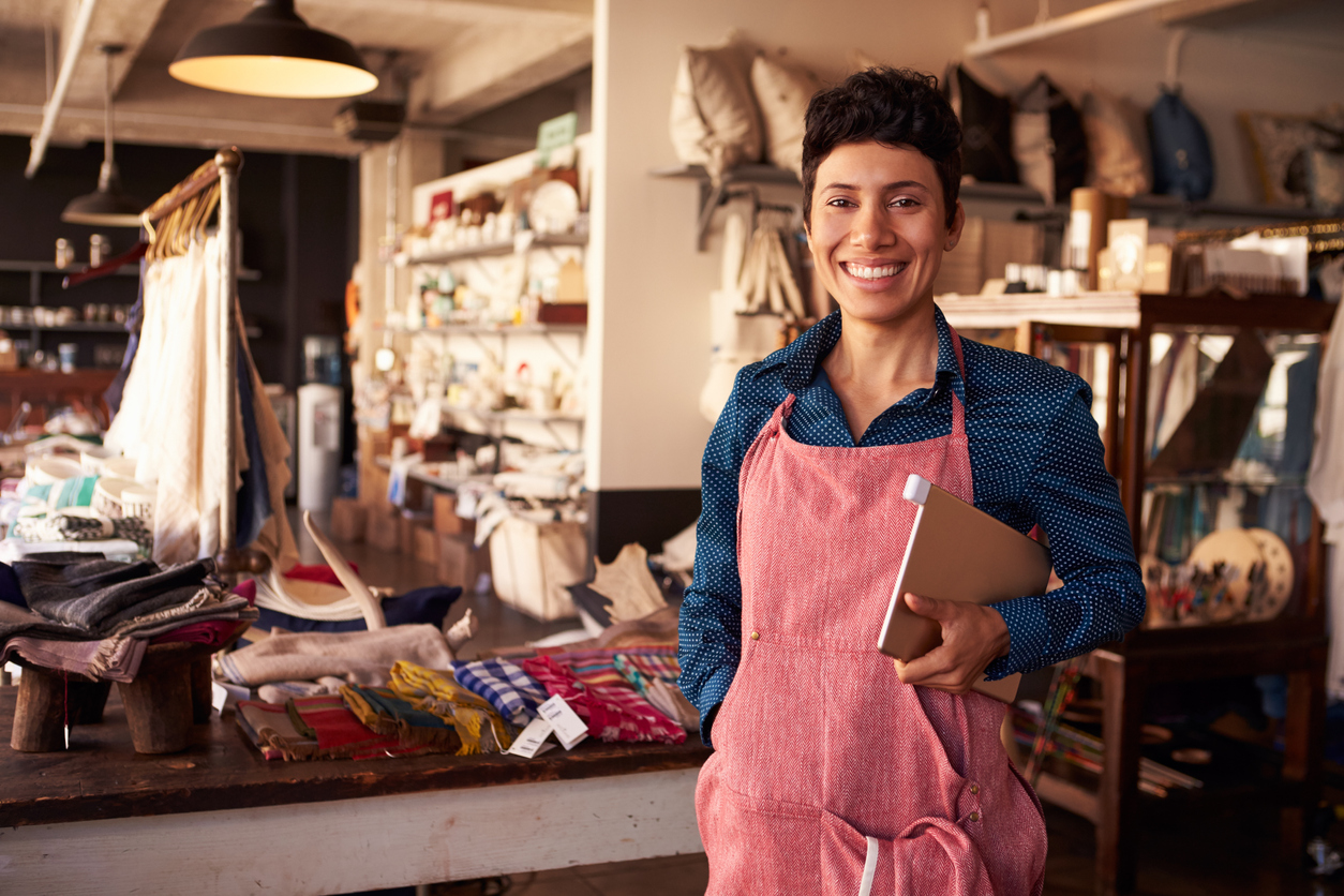 Portrait Of Female Owner Of Gift Store With Digital Tablet. Microloan vs payday loan
