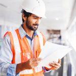 Ingeniero joven sosteniendo un contrato. Concept: ingresos de compañía de construcción