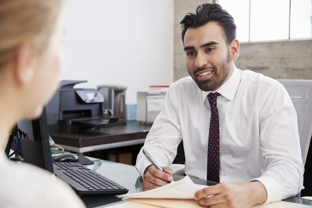 Young Hispanic male professional in meeting with woman in office. Concept: bookkeeping