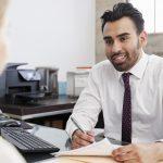 Hombre joven hipánico latino profesional en una junta con una mujer en una oficina. Concept: teneduría de libros