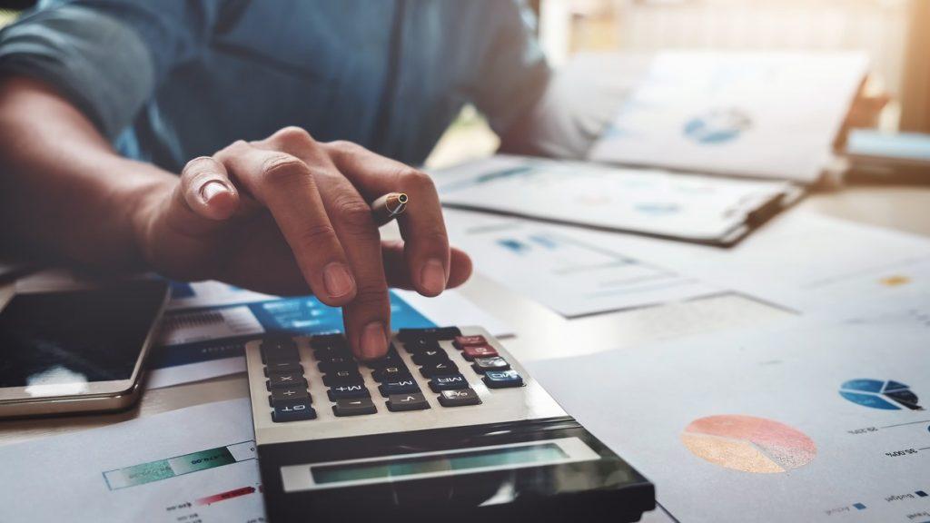 Concepto de contaduría de negocios. Hombre de negocios usando una calculadora con laptop en su oficina. Concept: teneduría de libros