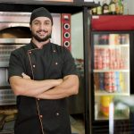 Latino restaurant owner posing near to oven smiling. Concept: restaurant business plan