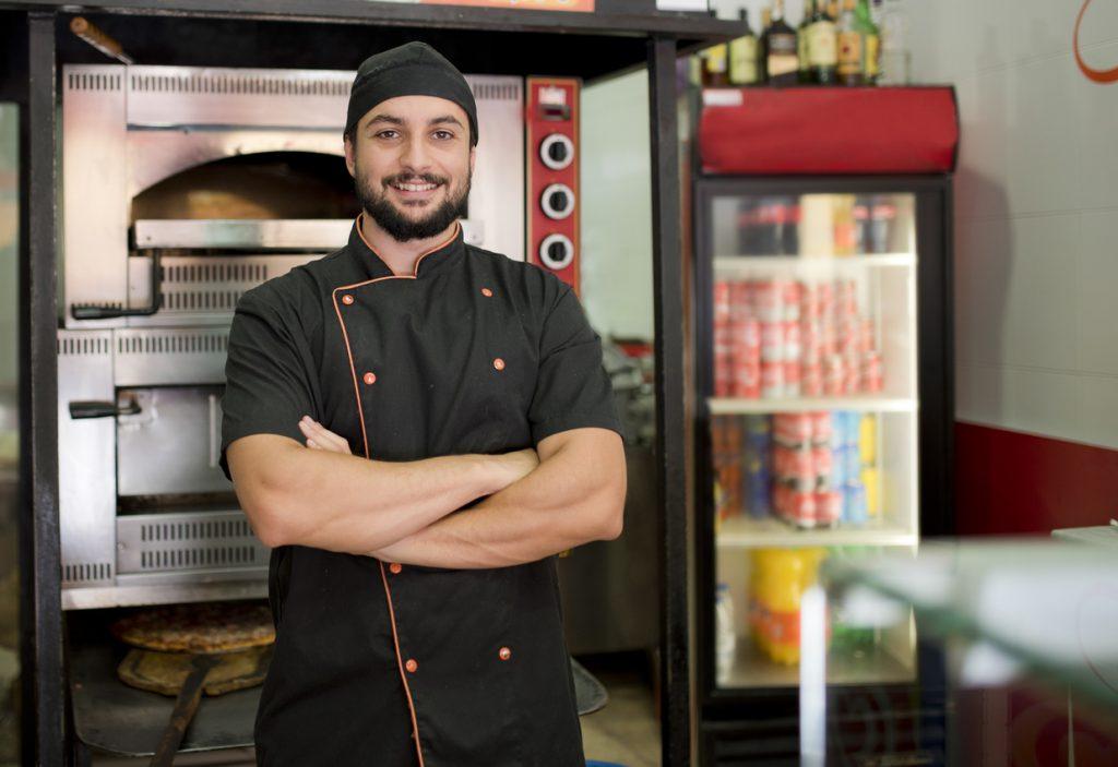 Dueño de restaurante latino posando frente al horno. Concepto: Plan de negocios restaurante