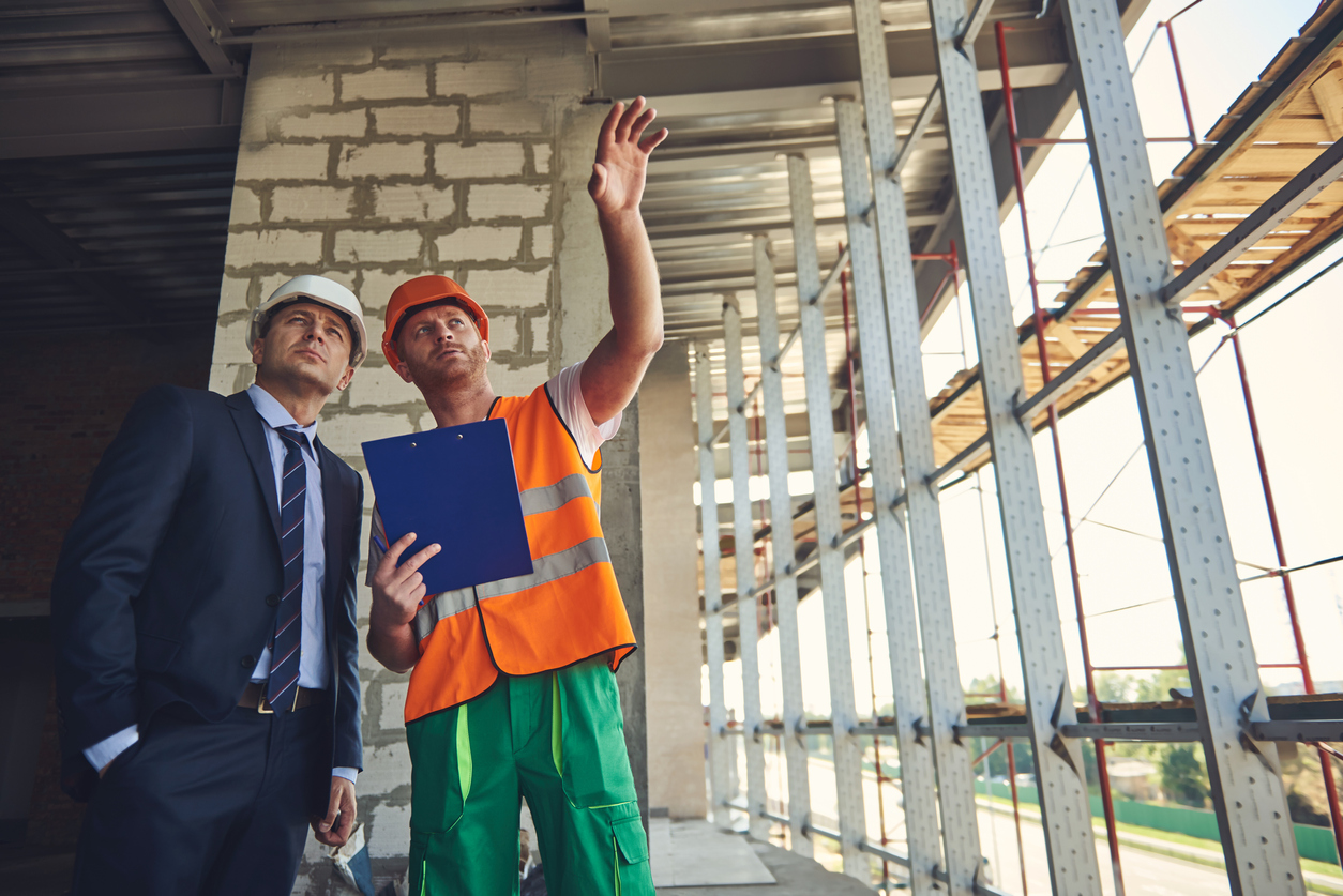 Worker man is showing to project manager completed design on construction site. Concept: business plan for construction company