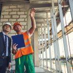 Obrero en lugar de obra mostando proyectos a capataz o inversor. Concepto: Plan de negocios para empresas de construcción