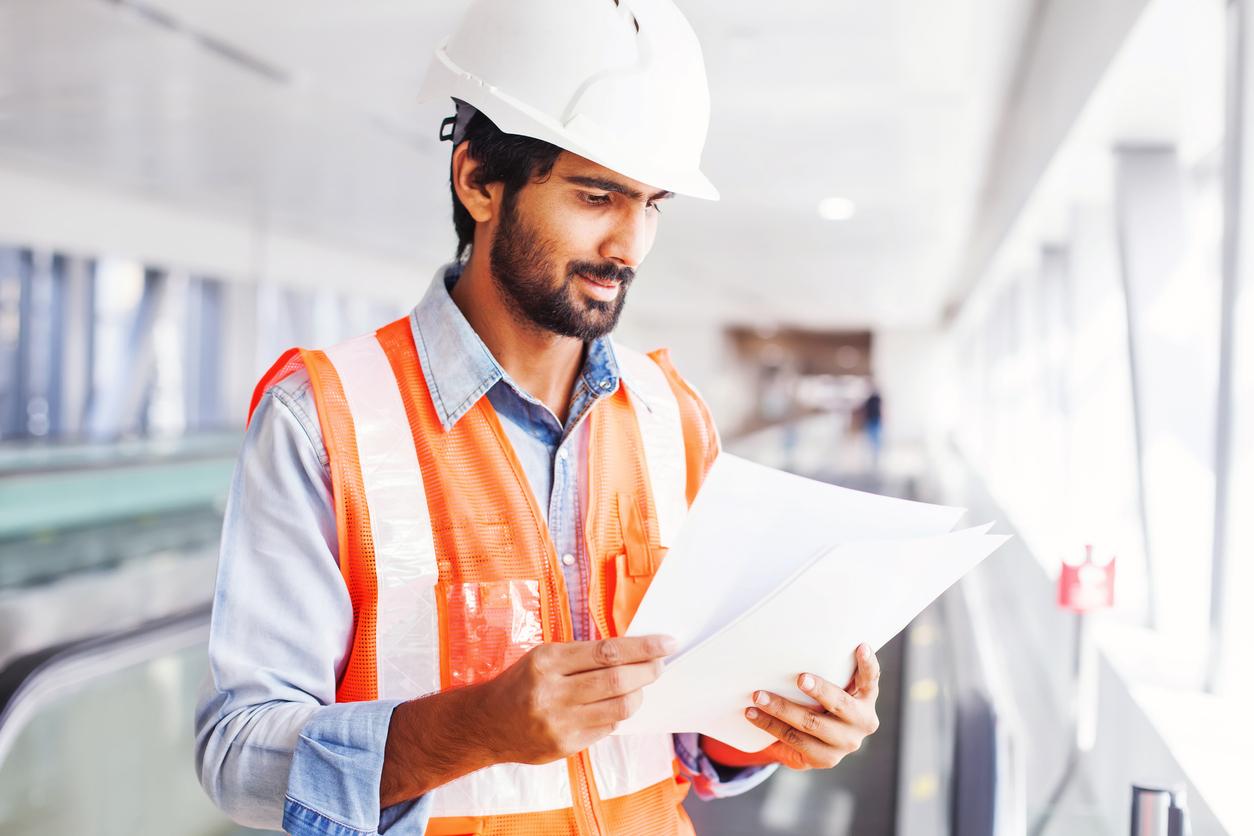 Trabajador de empresa de construcción revisando plan de negocios.