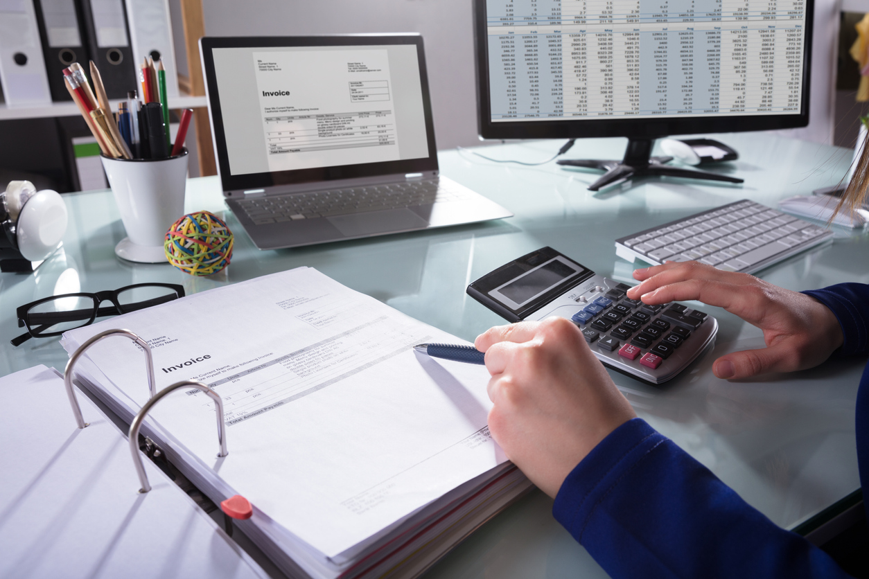 Close-up Of A Businessperson's Hand Calculating Invoice At Workplace. concept: small business bookkeeping, accounting