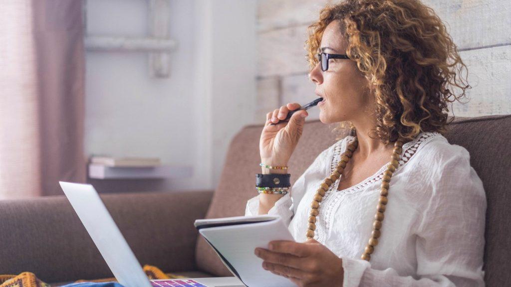 Mujer bella pensando y escribinedo en una libreta/cuaderno y en su laptop/computadora, en su oficina desde casa. concept: teneduría de libros y contabilidad