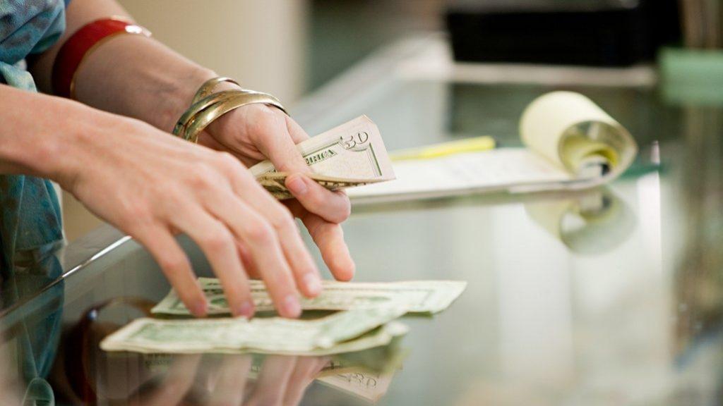 Mujer contando dinero en su negocio, pequeña empresa. Concept: préstamo fiscal.