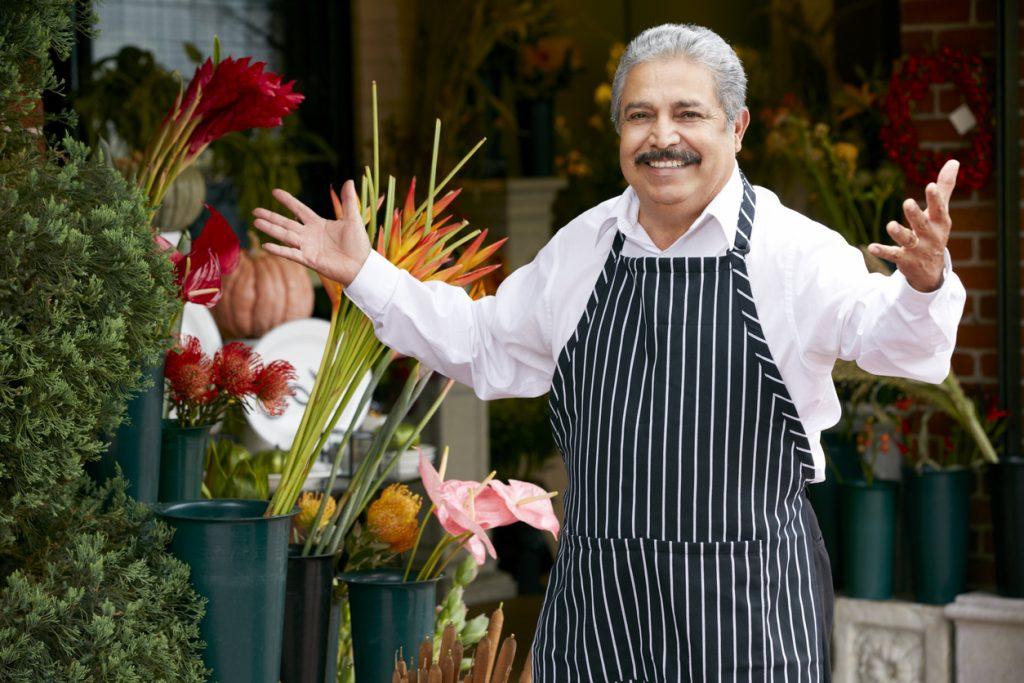 Dueño de floristería sonriente a la puerta de su negocio. Concepto: margen de ganancias.