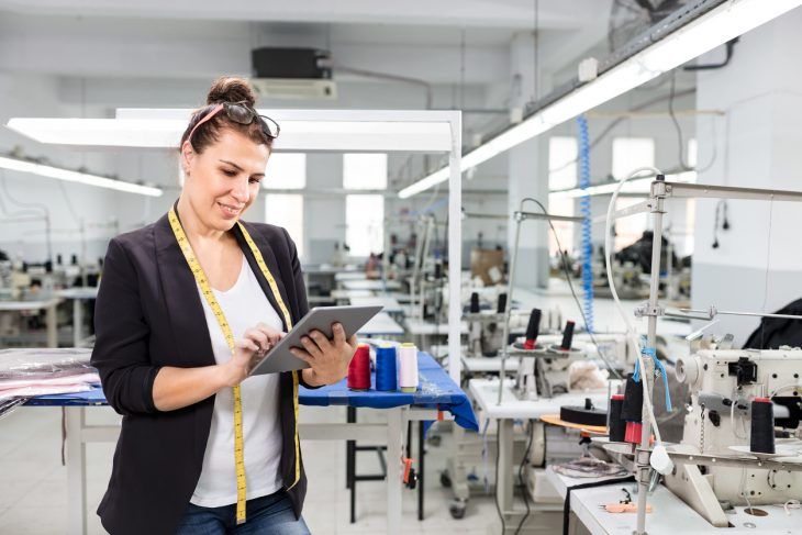 Small business owner working with tablet in textile factory. Concept: business plan and business loan