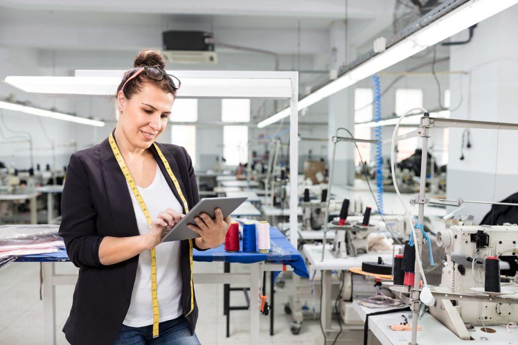 Empresaria en fábrica textil trabajando con tablet. Concepto: plan de negocios y préstamo comercial.