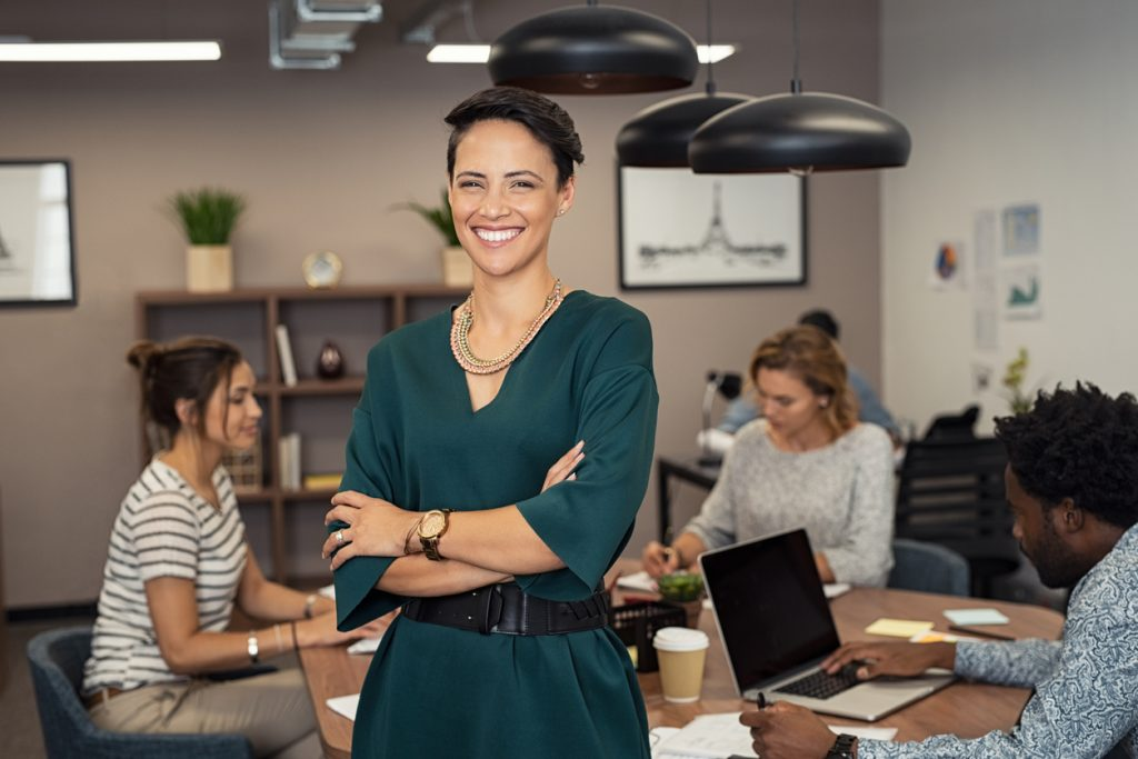 Portrait of successful business woman standing with her colleagues working in background at office. Portrait of cheerful fashion girl in green dress standing with folded arms and looking at camera. Beautiful businesswoman feeling proud and smiling. Concept: micrloans