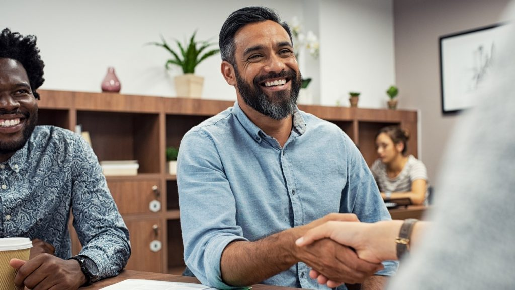 Two business people shaking hands while sitting in meeting room. Middle eastern businessman shake hands to businesswoman. Portrait of happy smiling latin man signing off deal with an handshake. Concept: microloans