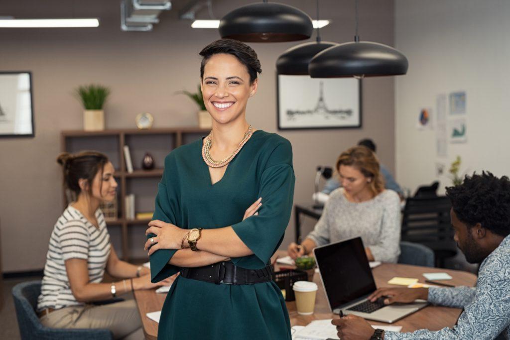 Retrato de mujer exitosa parada junto a su equipo de trabajo en su oficina. concept: micropréstamo