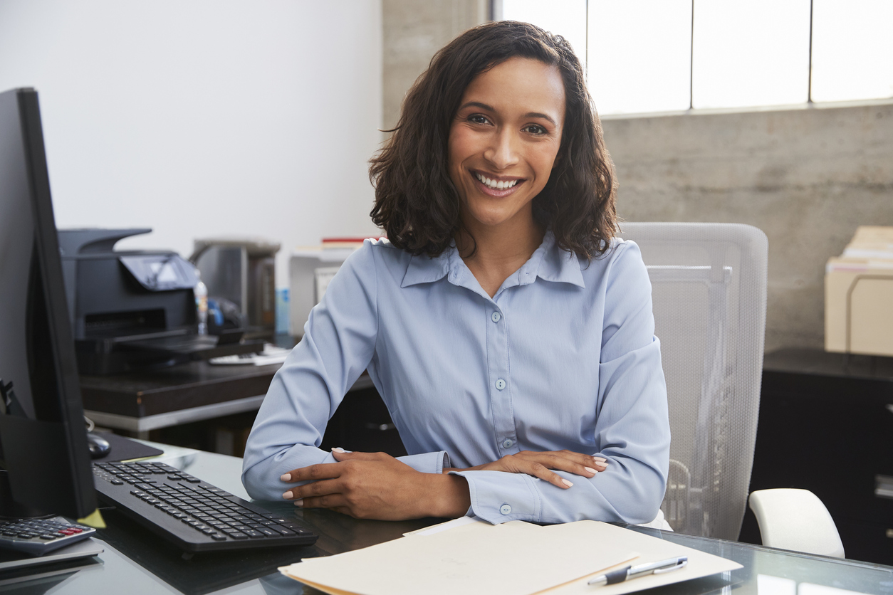 Young female professional at desk smiling to camera. concept: bookkeeper