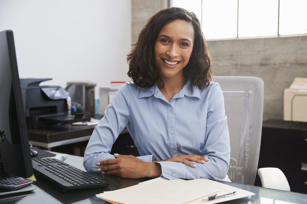 Profesionista joven en su escritorio sonriendo a la cámara. Concept: tenedor de libros