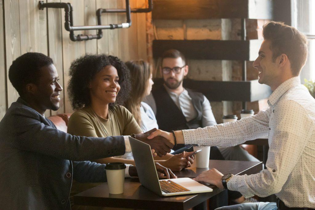 Hombre caucásico y hombre multiracial africano dándose la mano en una junta en un café. concept: Micropréstamos vs familiares y amigos