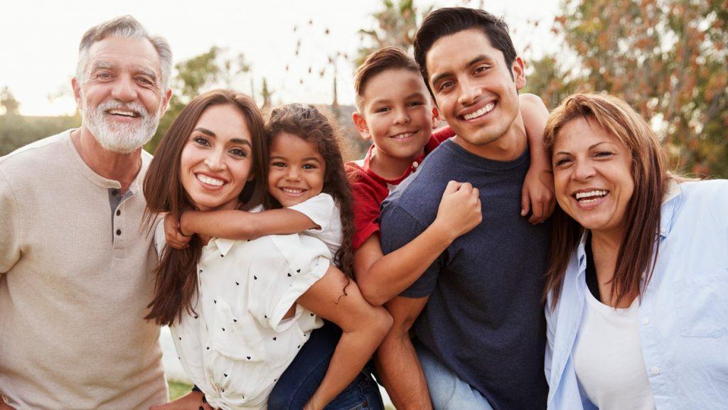 Familia de tres generaciones de hispánicos/latinos en un parque sonriendo a la cámara. Concept: Micropréstamos vs familiares y amigos