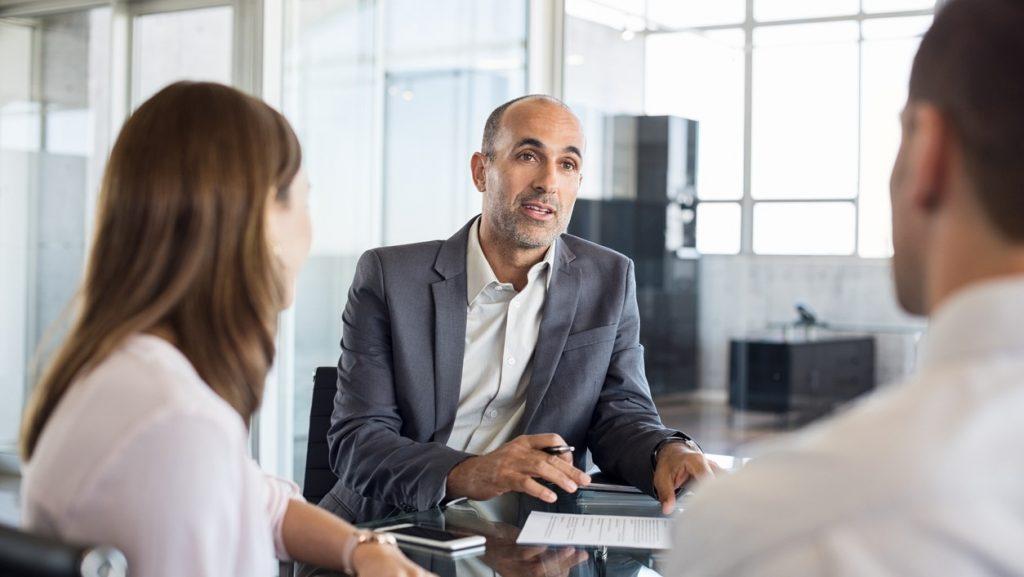 Agente financiero maduro hablando sobre financiamiento con empresario joven en una oficina. Concept: Micropréstamos vs familiares y amigos