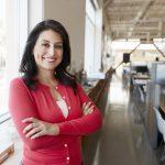 Arquitecta latina sonriendo en su oficina. Concept: Préstamos subsidiados vs préstamos no subsidiados