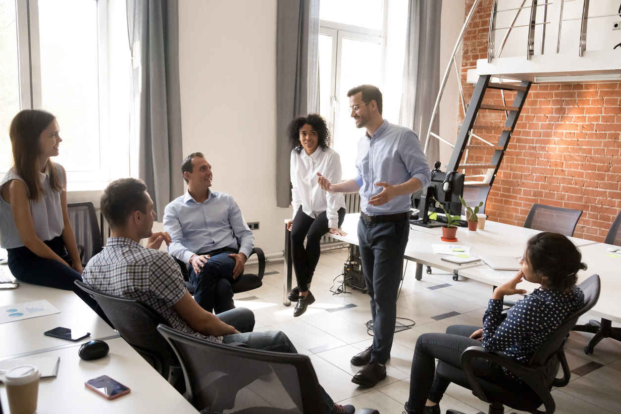 Confident business coach talking with multiracial group of office workers, having good conversation with subordinate, brainstorming, discussing business strategy, ideas, team building activity