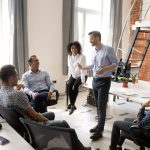 Business coach o coach de negocios hablando a empleados en oficina