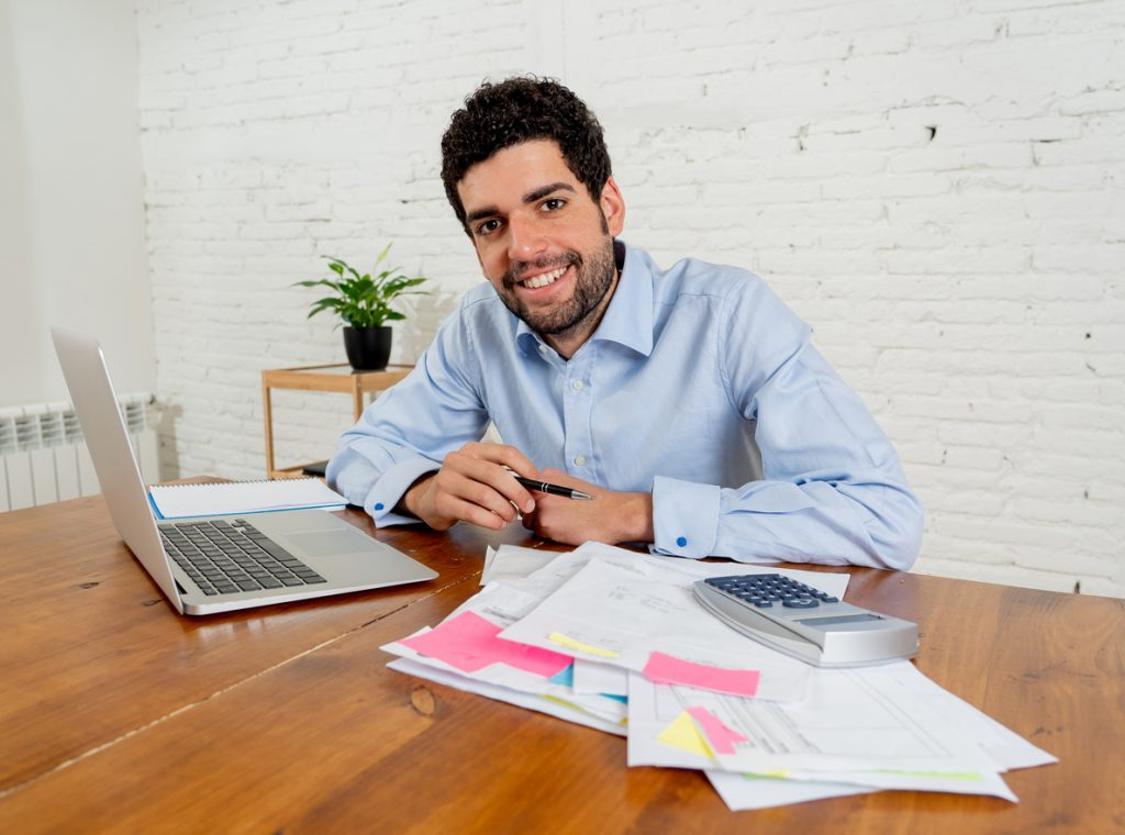 Happy attractive entrepreneur man calculating costs, charges, mortgage, taxes or paying bills with documents and laptop at home office. In online banking and Success business finances free of debts. Concept: microloan