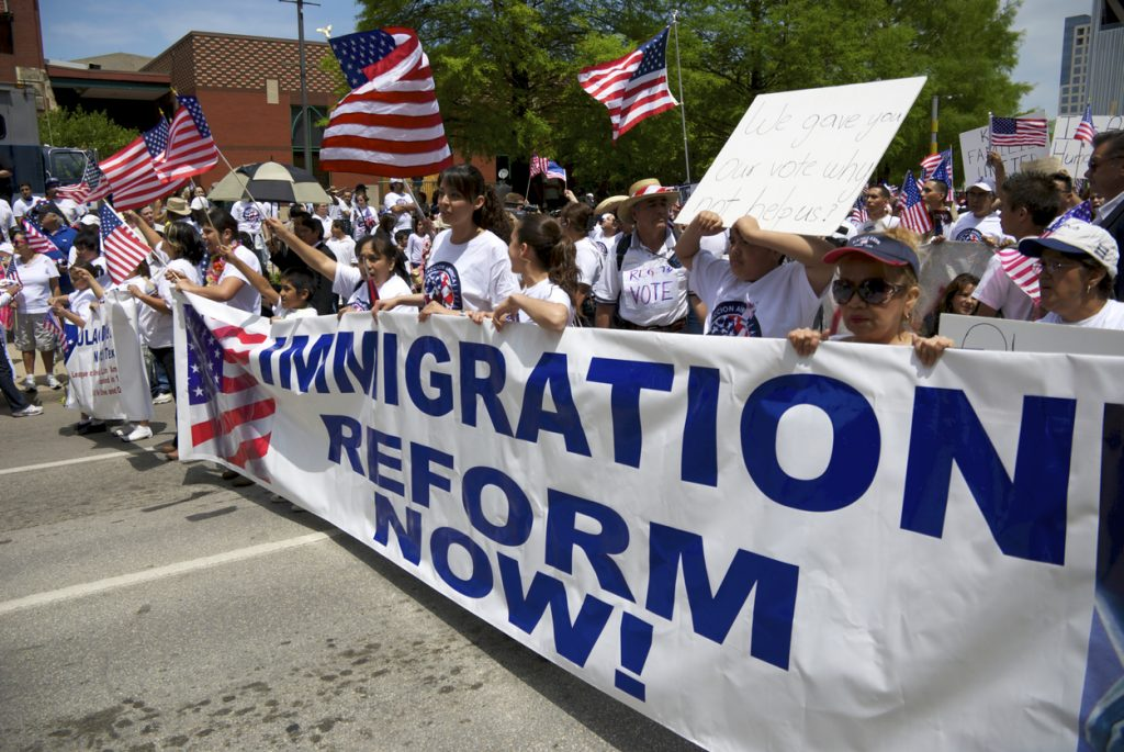 Demonstrators carry banners and wave flags during a pro-immigration march agains an imigration reform