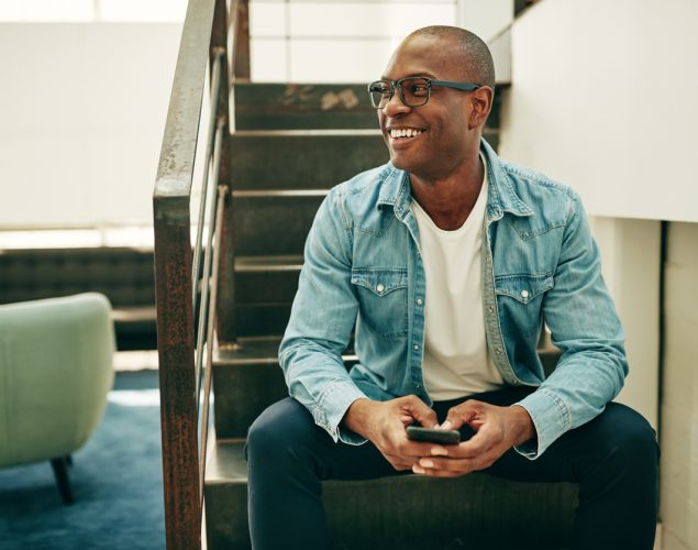 Smiling young African businessman wearing glasses and reading text messages on a cellphone while sitting on stairs in an office. Concept: solopreneur