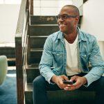 Empresario joven sonriendo, tiene gafas/lentes y un celular en la mano. Sentado en las escaleras de su oficina. Concept: solopreneur