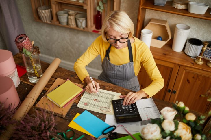 High angle portrait of female businesswoman counting finances using calculator in small shop, copy space. Concept: revise business plan to increase profit