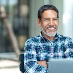 Portrait of happy mature man with white, grey stylish short beard looking at camera outdoor. Casual lifestyle of retired hispanic people or adult asian man smile with confident at coffee shop cafe. Concept: start a business as an immigrant