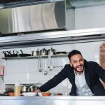 Happy young restaurant owner standing at kitchen counter looking away and smiling. Caucasian businessman in commercial kitchen. Concept: entrepreneur