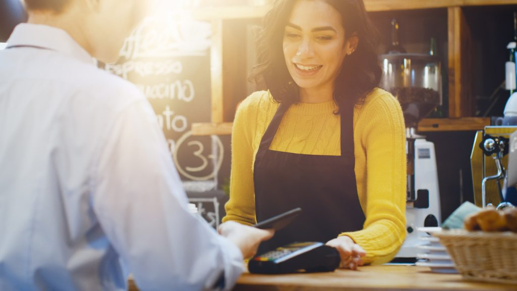 In the Cafe Beautiful Hispanic Woman Makes Takeaway Coffee For a Customer Who Pays by Contactless Mobile Phone to Credit Card System. Concept: debt to income ratio