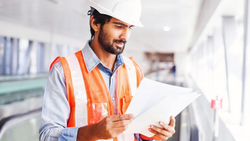 Ingeniero joven sosteniendo un contrato. Concept: relación deuda ingreso