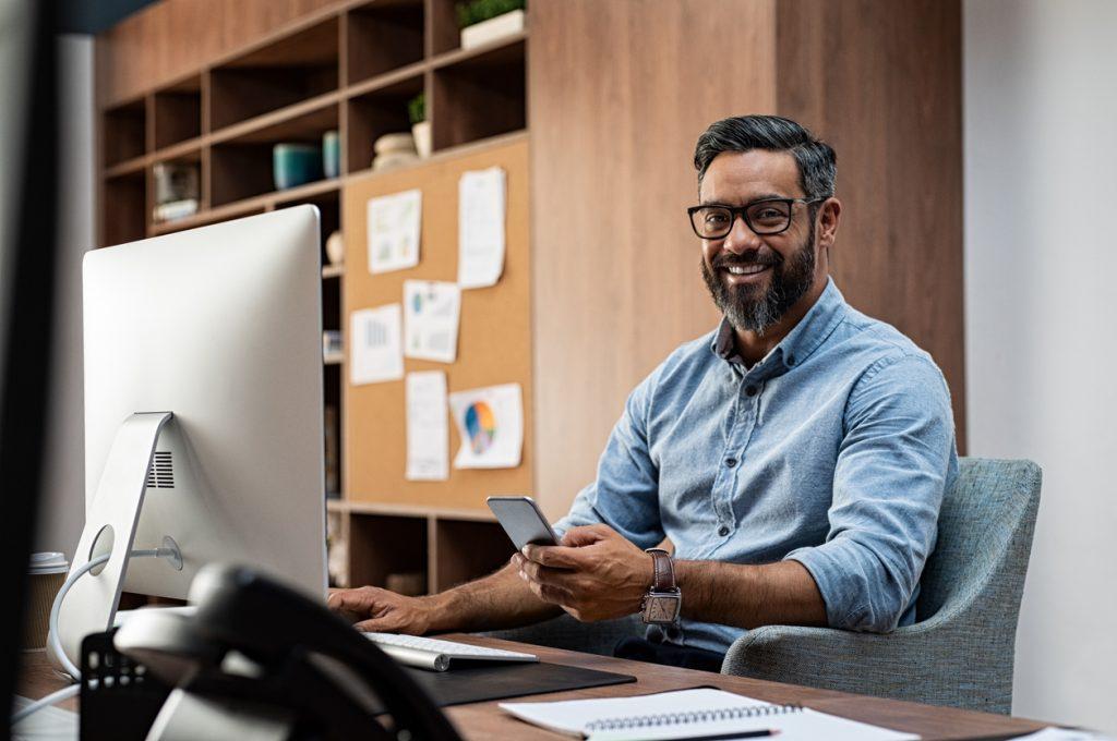 Hombre de negocios sonriendo mientras trabaja en su computadora de escritorio y hace una llamada en su smartphone. Concept: tipos de préstamos