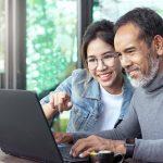 Hombre mayor y chica joven mirando computadora, joven enseñándo sobre computación a hombre mayor. concept: Roth IRA