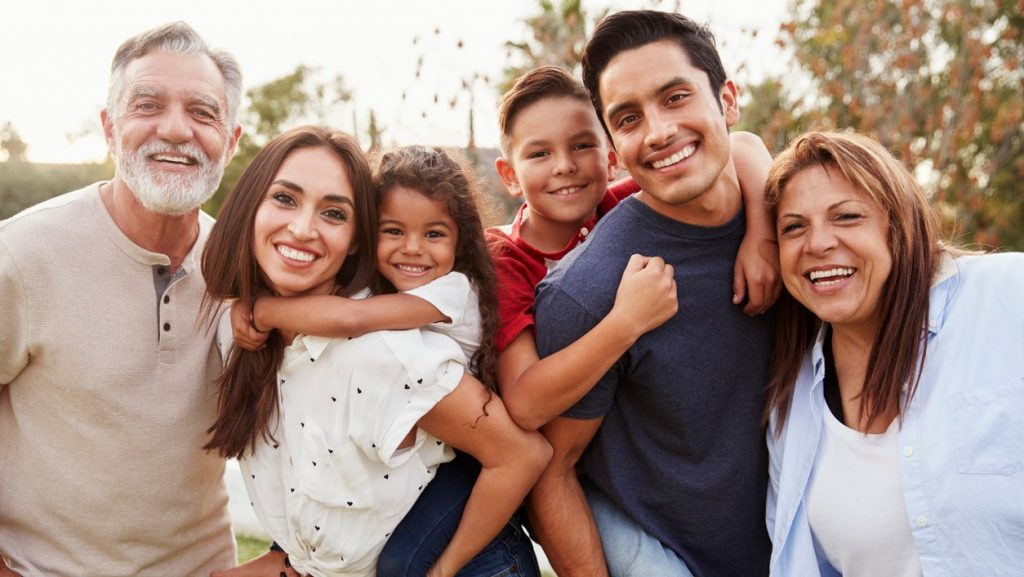 Three generation Hispanic family standing in the park, smiling to camera, selective focus. Concept: Roth IRA