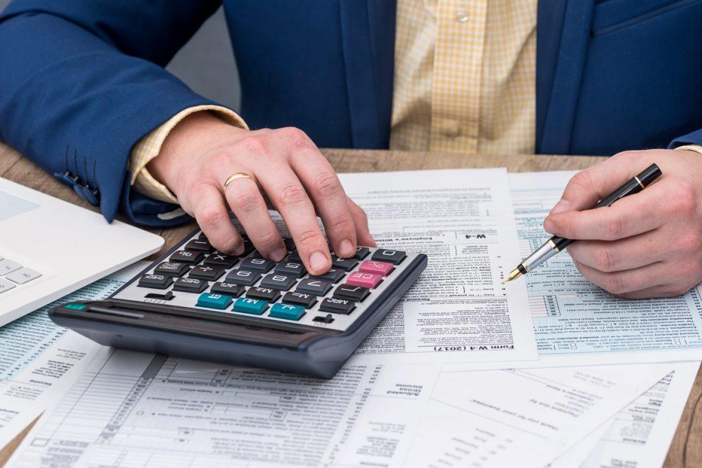 Hombre haciendo su declaración de impuestos, hojas, papeleo, calculadora. Concept: software de impuestos