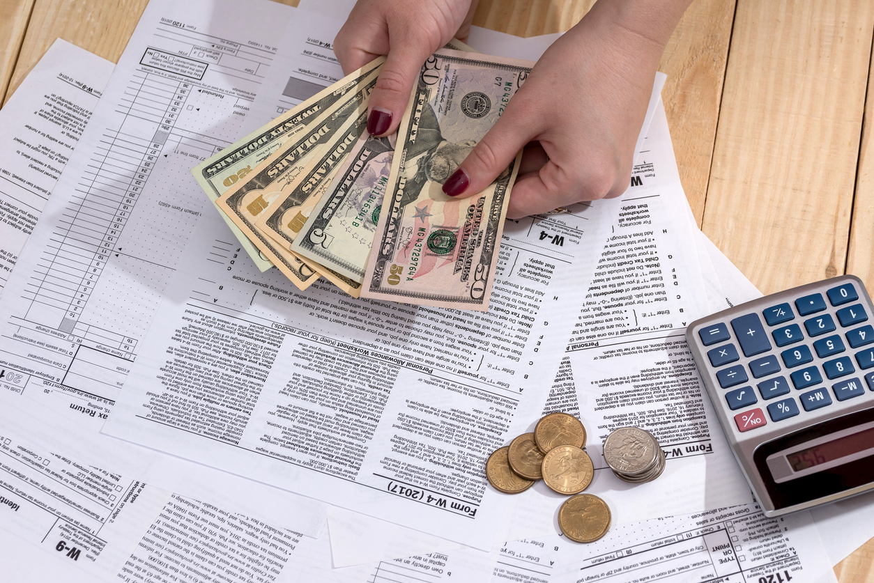 woman counting money on the background of tax return. Concept: What is nontaxable income?